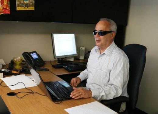 Person who is blind with opaque glasses uses laptop