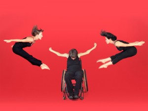 3 dancers, 2 are airborne their bodies forming < and > the third is a dancer in a wheelchair with arms outstretched.